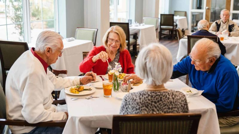 Seniors enjoying lunch in assisted living dining room