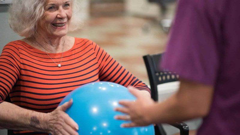 Senior woman holding rubber exercise ball with assisted living nurse