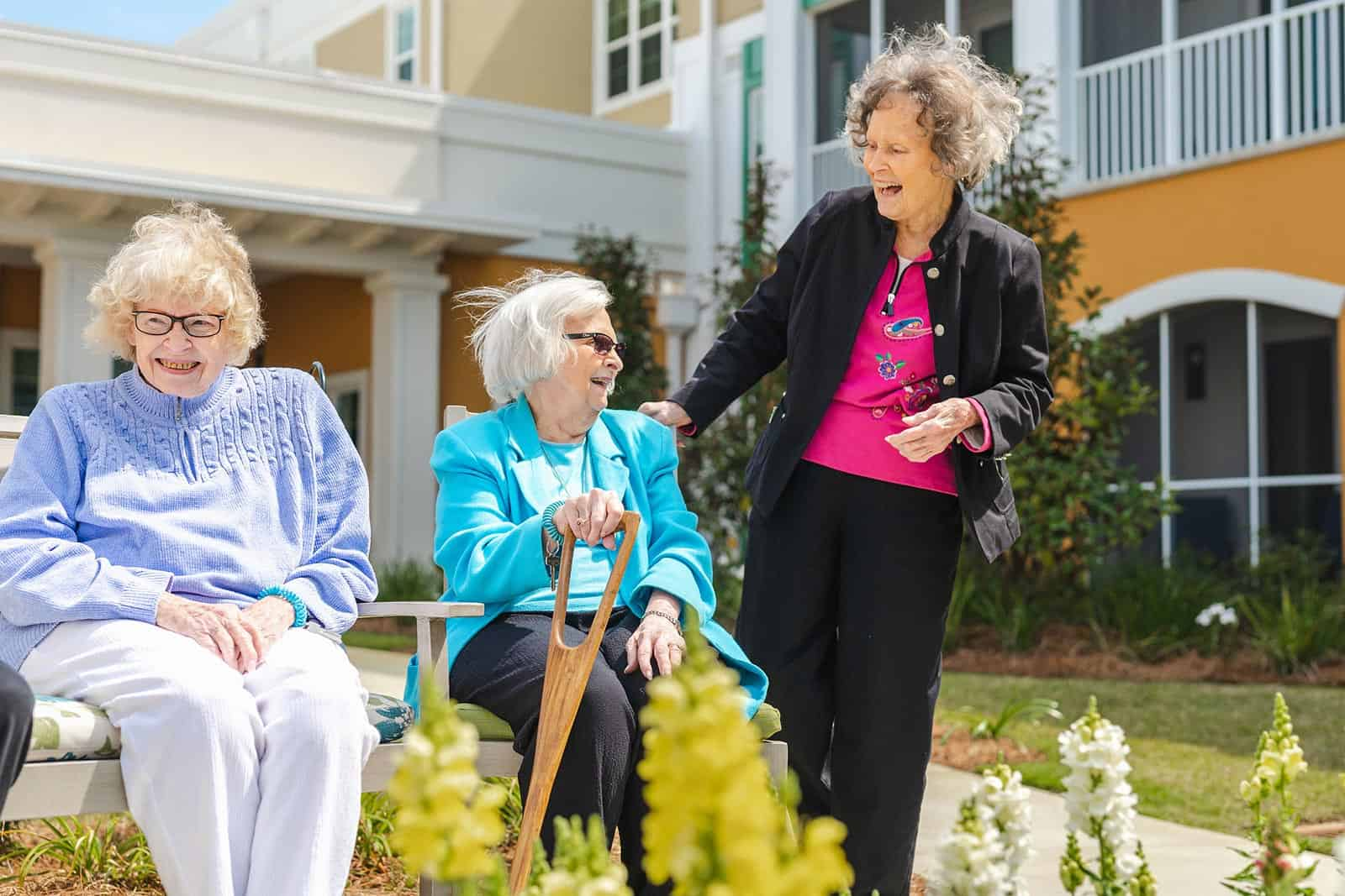 Three senior women socializing in assisted living community courtyard