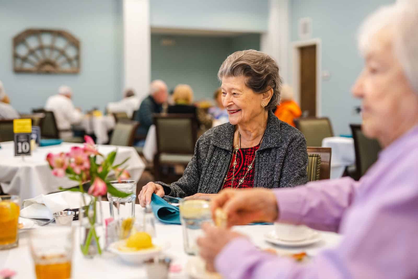 Smiling Senior Women Seated At Dining Table In Assisted Living Community Dining Room