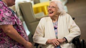 Nurse chatting with senior woman in wheelchair