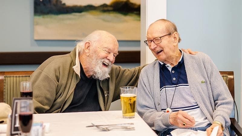 Senior men laughing over drinks