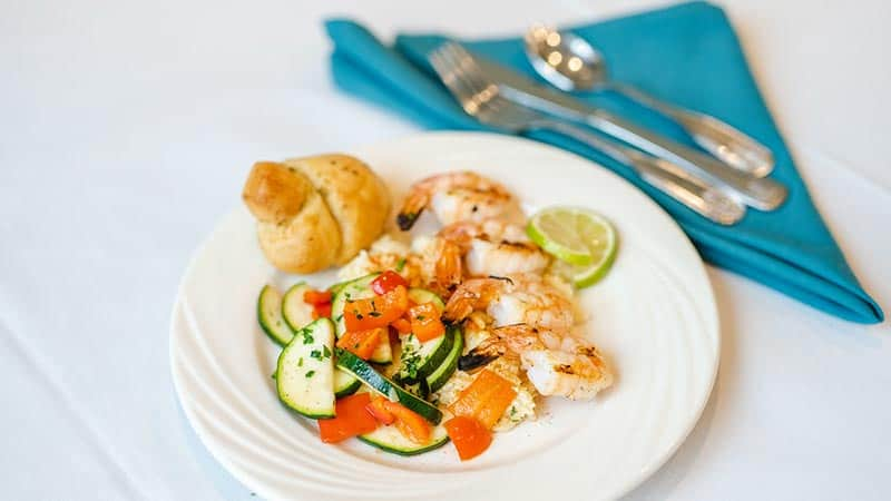 Shrimp and salad with biscuit, cloth napkin and cutlery
