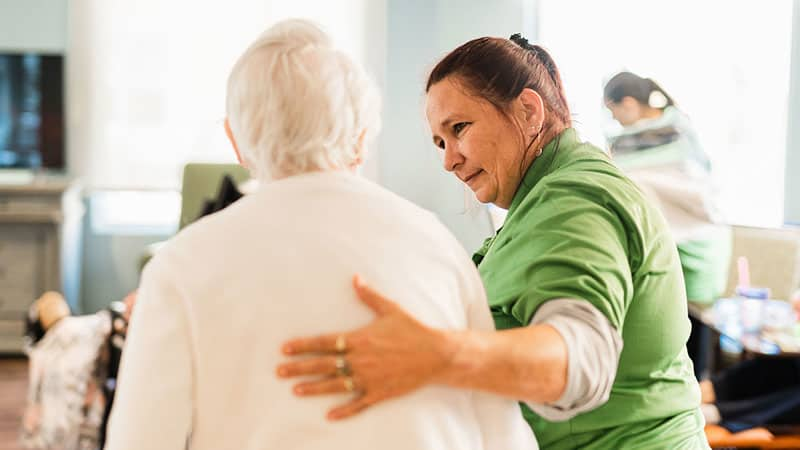 Staff member escorting senior woman in assisted living community