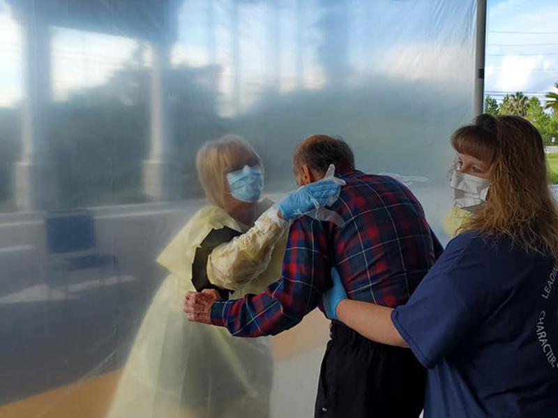 Senior man and family member hugging at visitation station during COVID-19